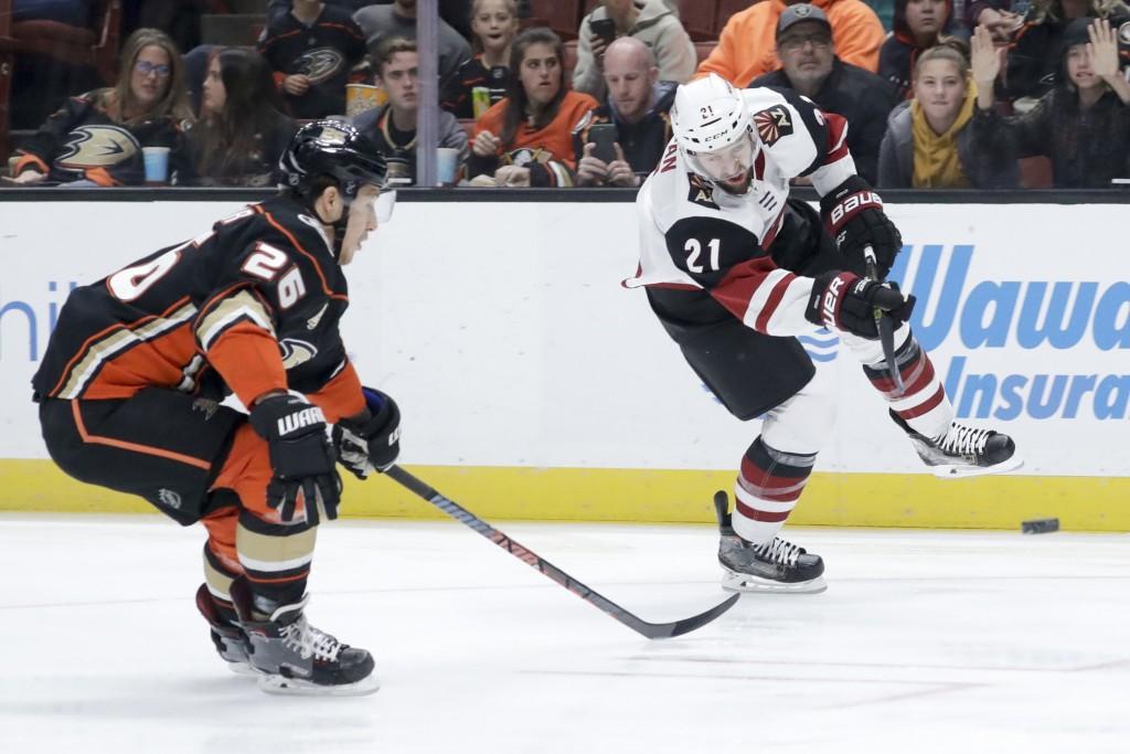 Arizona Coyotes center Derek Stepan, right, shoots past Anaheim Ducks defenseman Brandon Montour during the first period of an NHL hockey game in Anah...