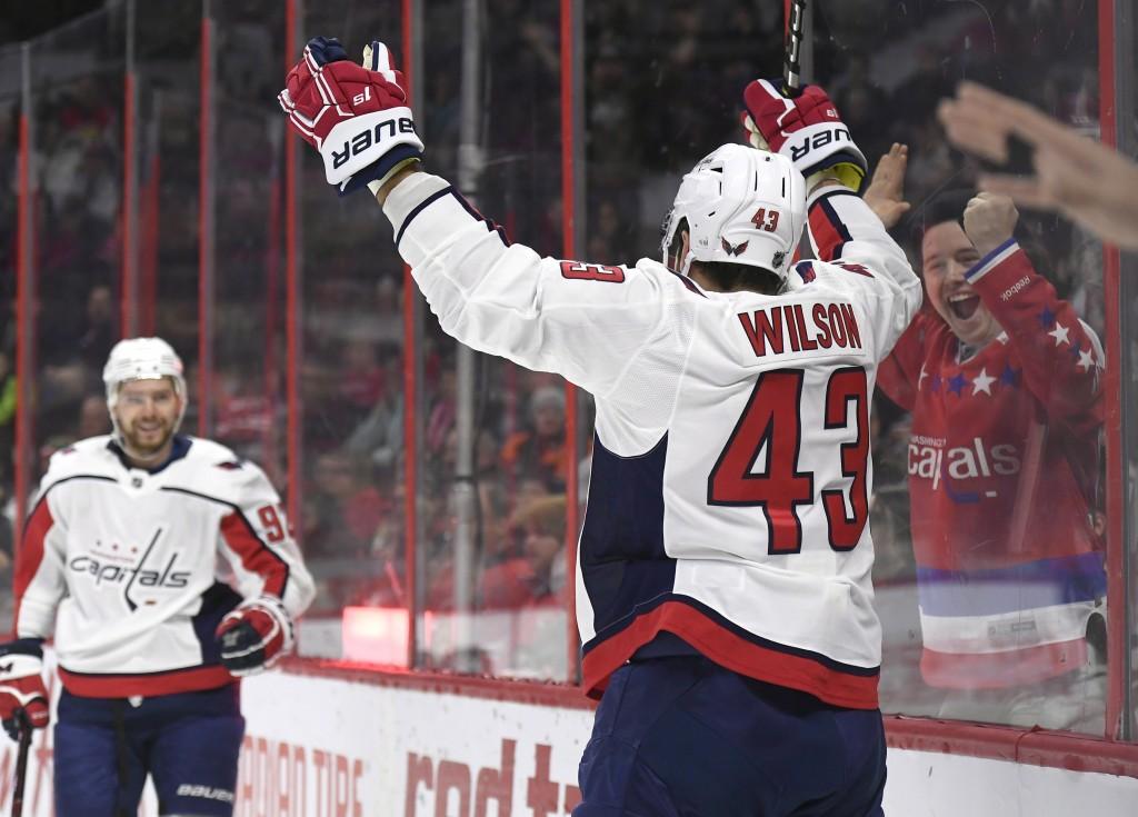 A fan cheers as Washington Capitals right wing Tom Wilson (43) celebrates his goal against the Ottawa Senators with center Evgeny Kuznetsov (92) durin...