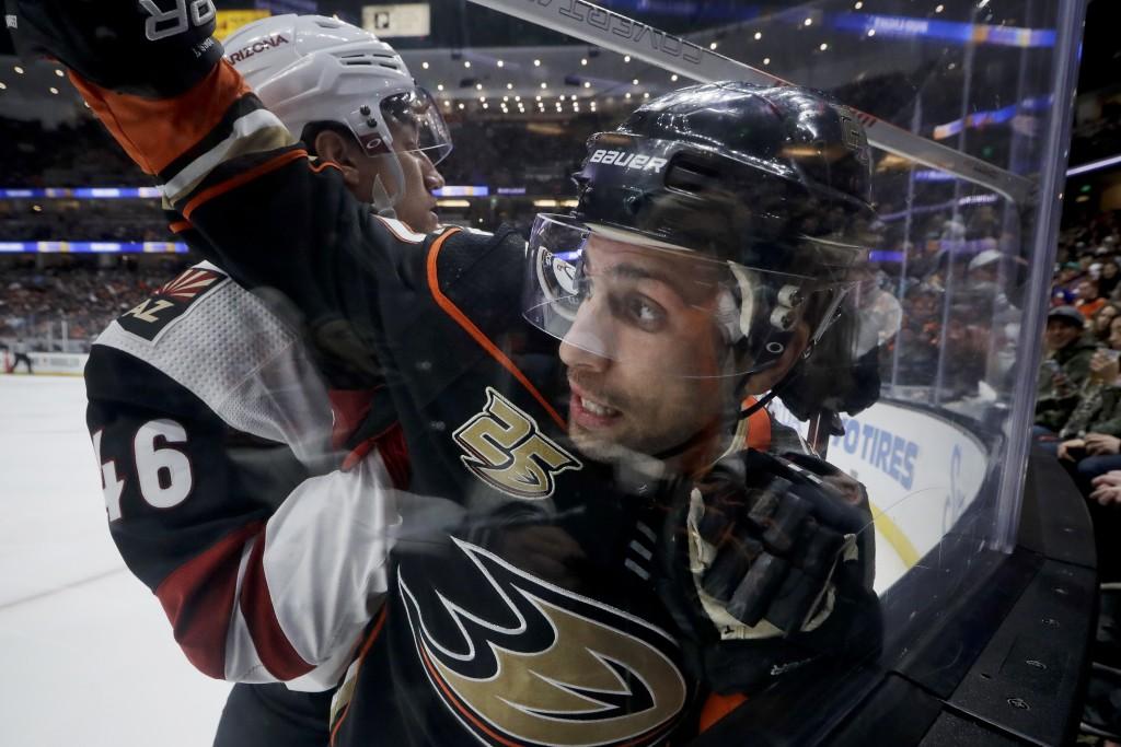 Arizona Coyotes defenseman Ilya Lyubushkin, left, checks Anaheim Ducks left wing Andrew Cogliano into the glass during the second period of an NHL hoc...