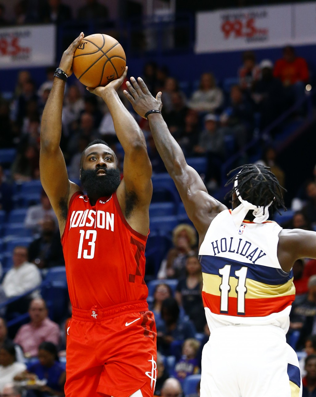 Houston Rockets guard James Harden (13)  shoots over New Orleans Pelicans guard Jrue Holiday (11) during the first half of an NBA basketball game, Sat...