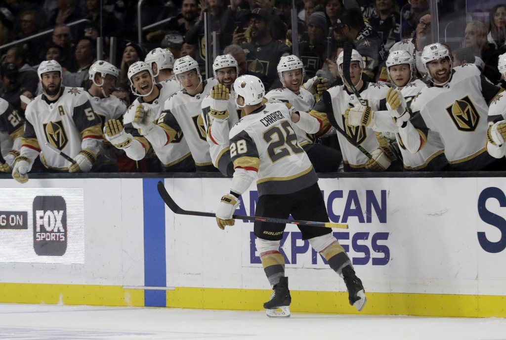 Vegas Golden Knights' William Carrier (28) celebrates with teammates after scoring against the Los Angeles Kings during the first period of an NHL hoc...
