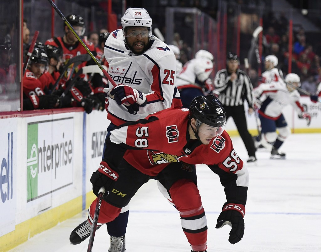 Washington Capitals right wing Devante Smith-Pelly (25) and Ottawa Senators defenseman Maxime Lajoie (58) battle for the puck during the first period ...