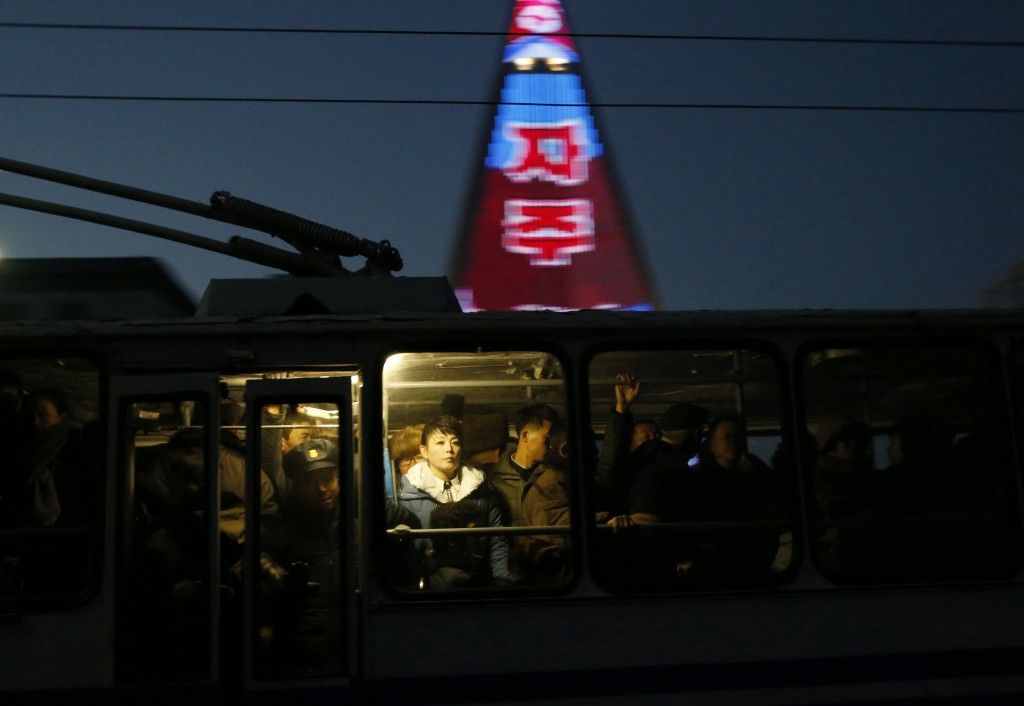 In this Dec. 20, 2018 photo, people ride on a tram as a propaganda message is partially seen displayed on the facade of the pyramid-shaped Ryugyong Ho...