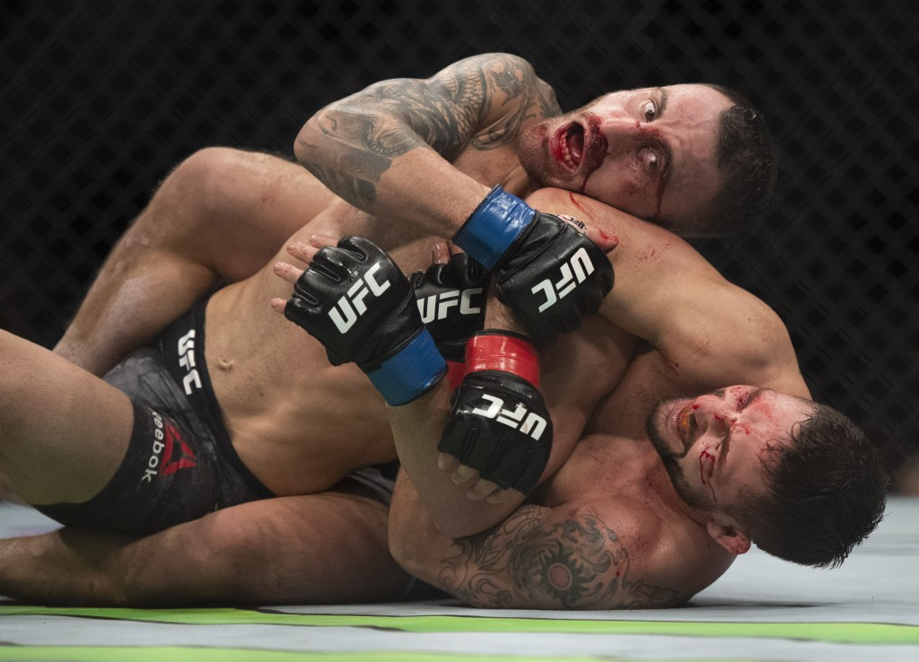 Alexander Volkanovski, top, tries to escape a submission attempt by Chad Mendes during the second round of a featherweight mixed martial arts bout at ...