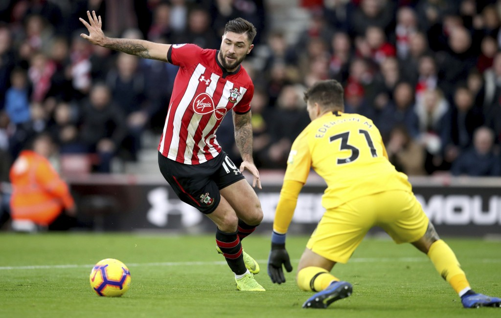 Southampton's Charlie Austin, left, tries to reach the ball ahead of Manchester City goalkeeper Ederson, during their English Premier League soccer ma...