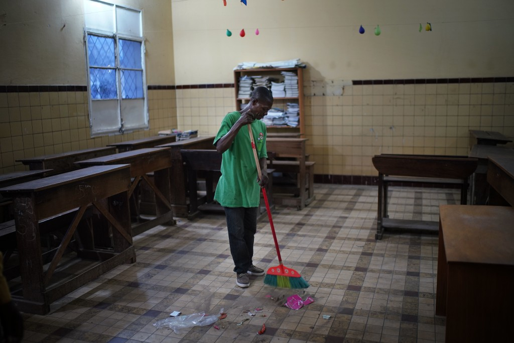 A cleaner sweeps the floors of a school classroom being prepared as a polling station in Kinshasa, Congo, Saturday Dec. 29, 2018.  Congolese people ar...