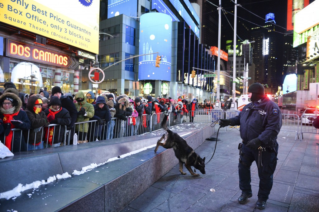 FILE - In this Dec. 31, 2017, file photo, a police K-9 unit patrols in New York's Times Square where crowds were gathered for the annual New Year's Ev...