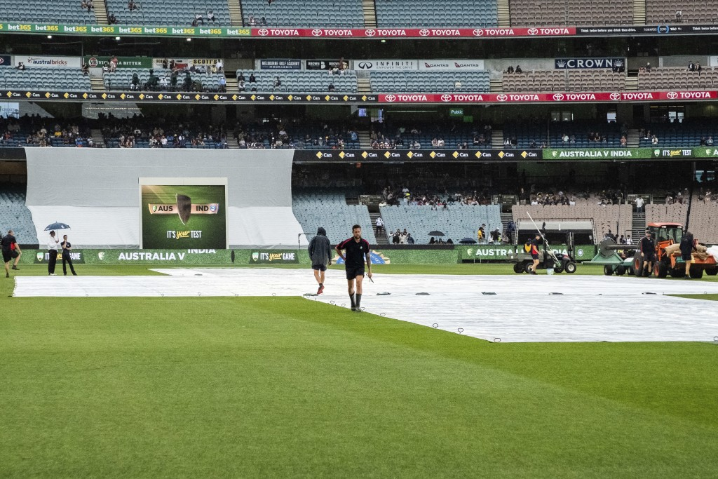 Melbourne cricket ground curating staff place pegs into the rain covers as the start of play is delayed during day five of the third cricket test betw...