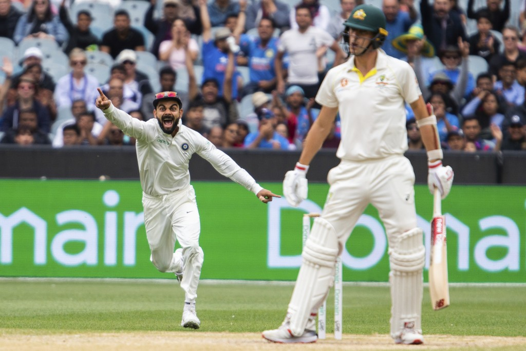 India's Virat Kohli, left, reacts after getting the wicket of Australia's Pat Cummins during play on day five of the third cricket test between India ...