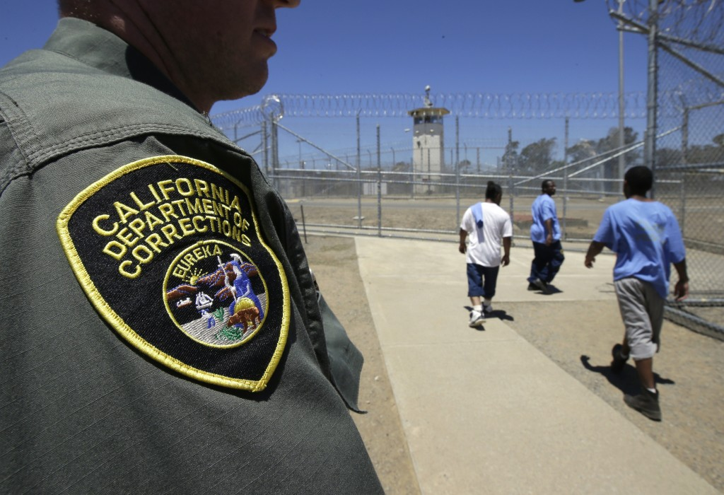 FILE - In this June 20, 2018 file photo, inmates pass a correctional officer as they leave an exercise yard at the California Medical Facility in Vaca...