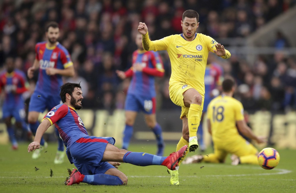 Chelsea's Eden Hazard is challenged by Crystal Palace's James Tomkins, left, during their English Premier League soccer match at Selhurst Park in Lond...