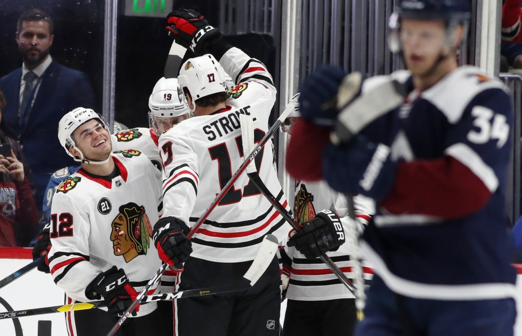 Chicago Blackhawks left wing Alex DeBrincat, left, is congratulated after scoring a goal by centers Jonathan Toews, back right, and Dylan Strome in th...