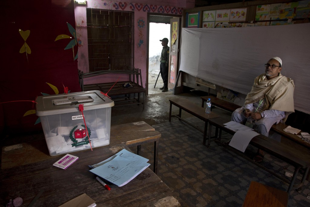 A Bangladeshi polling official waits for voters next to a ballot box at a polling station in the ancient city of Panam Nagar, about 20 kilometers (12 ...