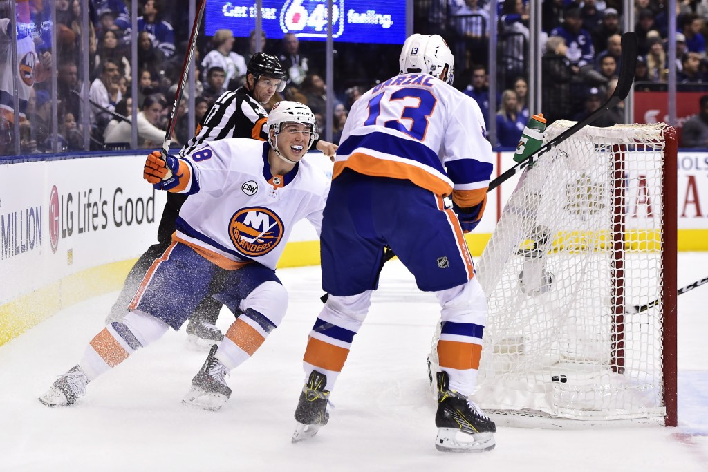 New York Islanders center Mathew Barzal (13) celebrates his goal against the Toronto Maple Leafs with teammate Anthony Beauvillier during the second p...