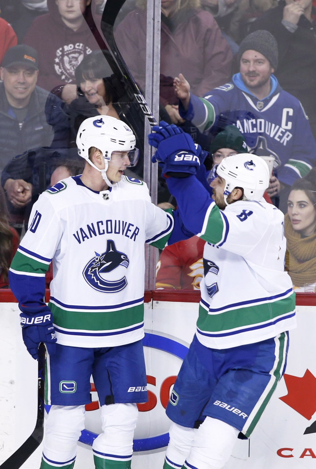 Vancouver Canucks' Elias Pettersson, left, celebrates his goal against the Calgary Flames with Christopher Tanev during the second period of an NHL ho...