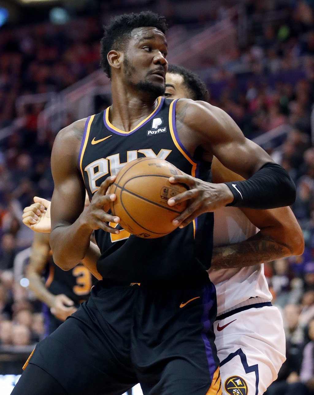 Phoenix Suns center Deandre Ayton (22) backs against the Denver Nuggets during the second half of an NBA basketball game, Saturday, Dec. 29, 2018, in ...