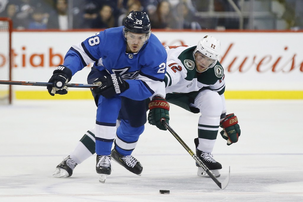 Minnesota Wild's Eric Staal (12) defends against Winnipeg Jets' Jack Roslovic (28) during second period NHL action in  Winnipeg, Manitoba, on Saturday...
