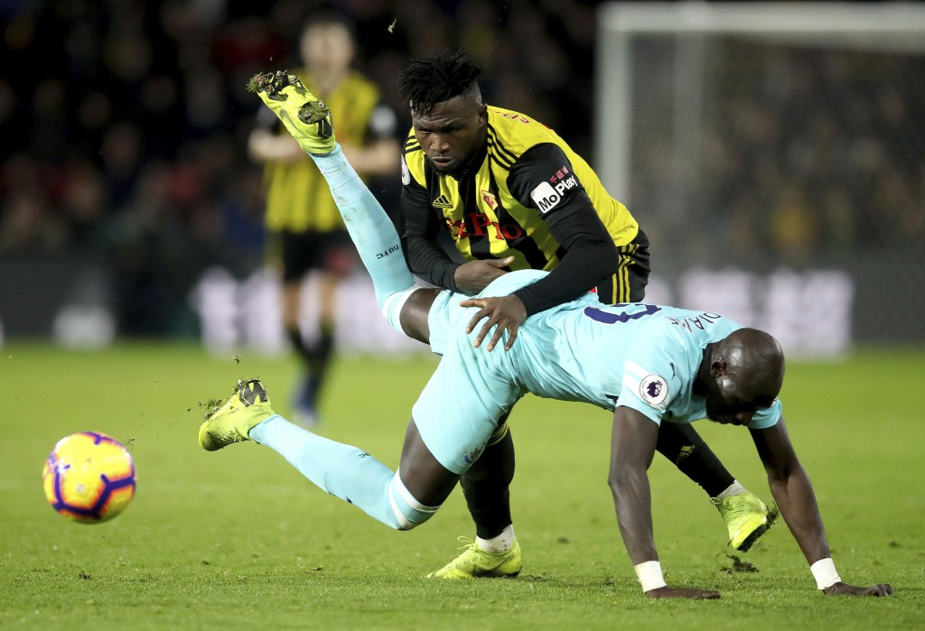 Newcastle United's Mohamed Diame falls under pressure from Watford's Isaac Success, during their English Premier League soccer match, at Vicarage Road...
