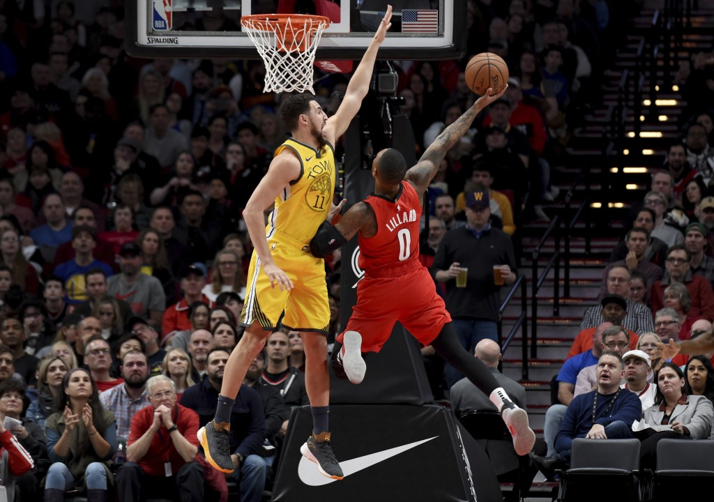 Portland Trail Blazers guard Damian Lillard, right, puts up a shot on Golden State Warriors guard Klay Thompson, left during the first half of an NBA ...