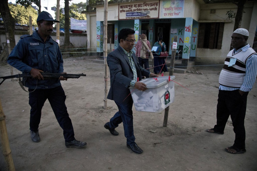 A Bangladeshi polling official carries a ballot box after the polling ended at a polling station in the ancient city of Panam Nagar, about 20 kilomete...