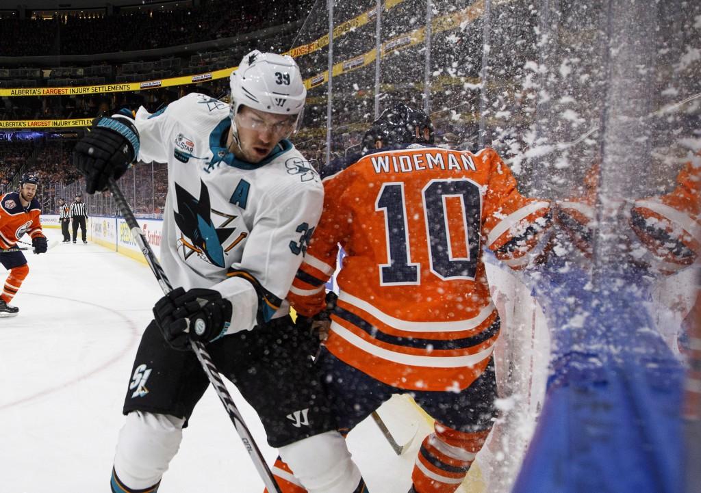 San Jose Sharks' Logan Couture (39) checks Edmonton Oilers' Chris Wideman (10) during the first period of an NHL hockey game, Saturday, Dec. 29, 2018 ...