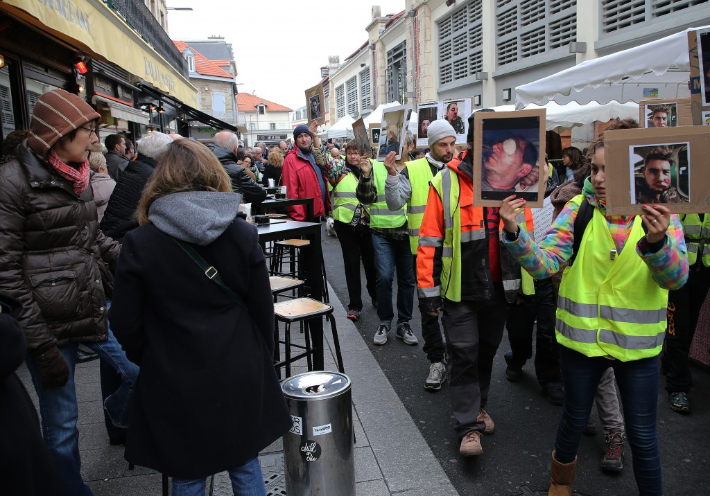 Demonstrators wearing yellow vest hold photos of people they say are victims of police violence in recent weeks in France, in Biarritz, southwestern F...