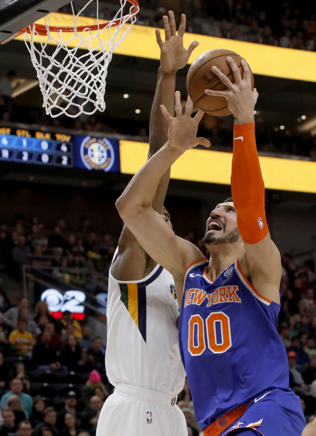 New York Knicks' Enes Kanter (00) attempts a layup as Utah Jazz's Derrick Favors, left, defends in the first half of an NBA basketball game on Saturda...