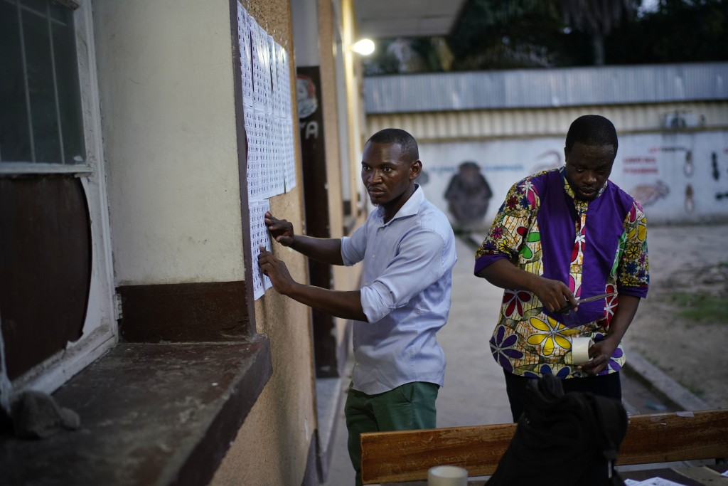 Election volunteers tape the list of registered voters at the entrance to a polling station in Kinshasa, Congo, Saturday Dec. 29, 2018.  Congolese peo...