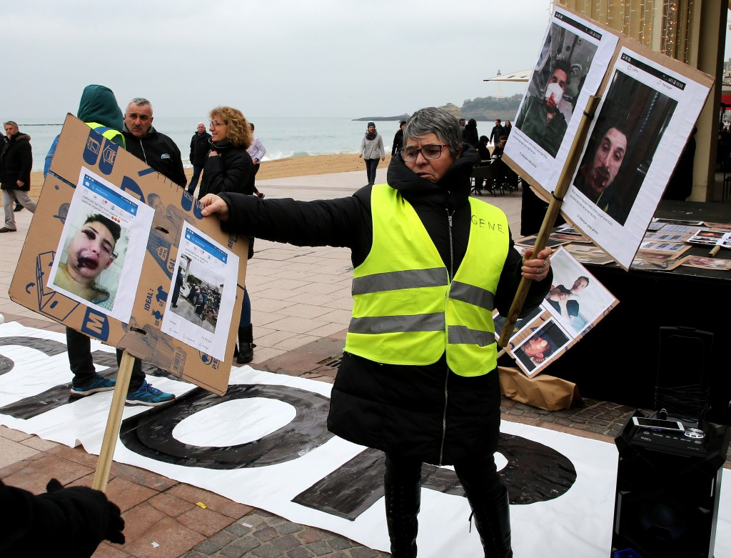A demonstrator wearing yellow vest holds photos showing who they say are victims of police violence in recent weeks in France, in Biarritz, southweste...