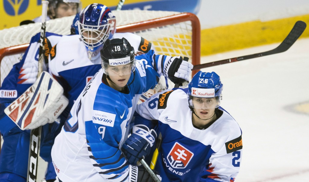 Slovakia's Milos Roman (26) tries to clear Finland's Rasmus Kupari (19) from in front of Slovakia goaltender Samuel Hlavaj (2) during the second perio...