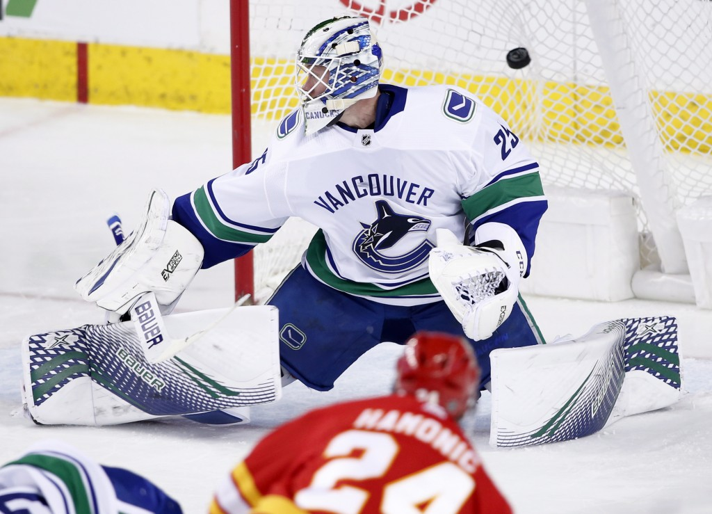 Vancouver Canucks goalie Jacob Markstrom, from Sweden, gives up a goal to Calgary Flames' Travis Hamonic during the second period of an NHL hockey gam...