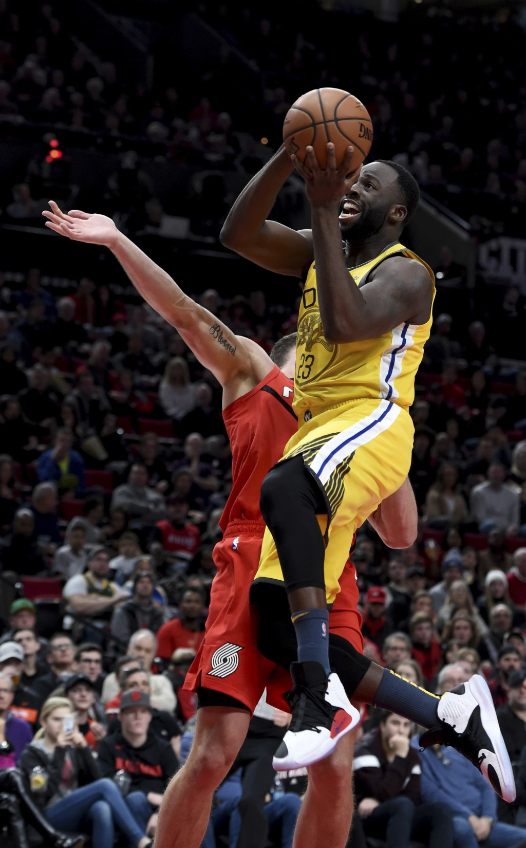 Golden State Warriors forward Draymond Green, right, drives to the basket on Portland Trail Blazers forward Meyers Leonard, left, during the first hal...