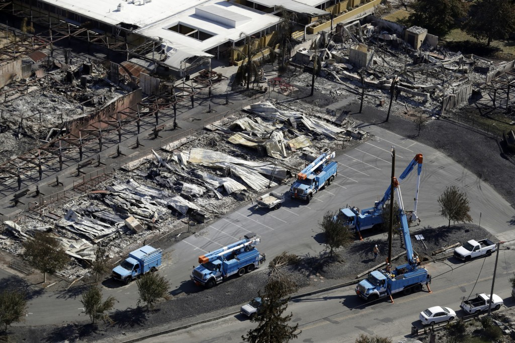FILE - In this Oct. 14, 2017, file photo, PG&E crews work on restoring power lines in a fire ravaged neighborhood in an aerial view in the aftermath o...