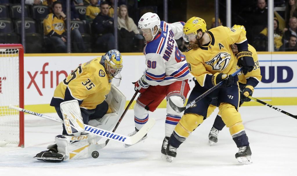 New York Rangers center Vladislav Namestnikov (90), of Russia, and Nashville Predators defenseman Ryan Ellis (4) reach for the rebound after Predators...