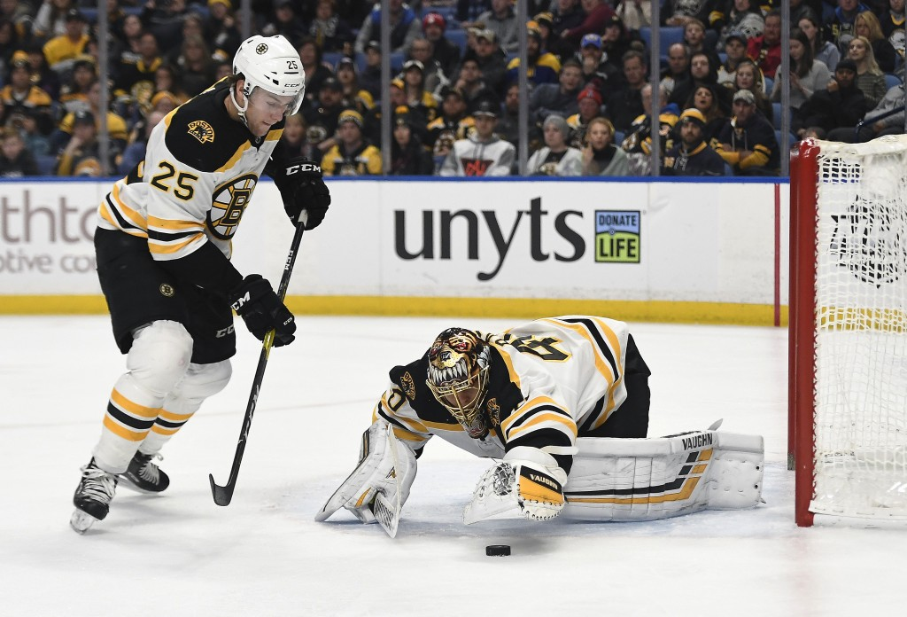 Boston Bruins goalie Tuukka Rask, right, reaches for a loose puck as the play is covered by defenseman Brandon Carlo (25) during the second period of ...