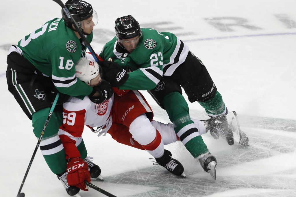 Detroit Red Wings left wing Tyler Bertuzzi (59) is squeezed by Dallas Stars center Tyler Pitlick (18) and defenseman Esa Lindell (23) during the first...