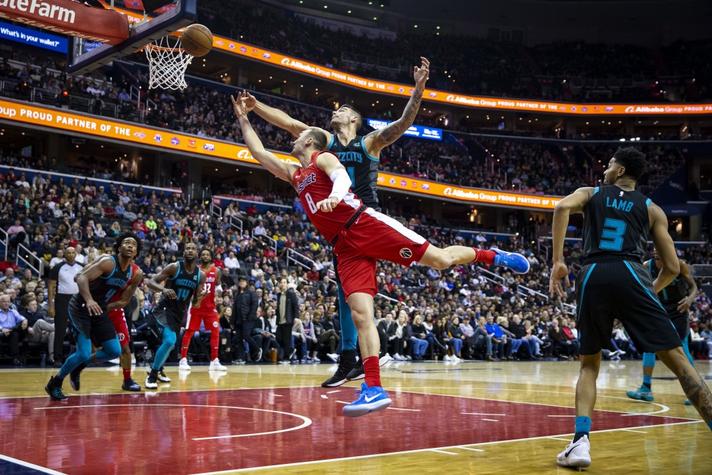 Washington Wizards forward Sam Dekker (8) attempts a layup past Charlotte Hornets center Willy Hernangomez (41) and guard Jeremy Lamb (3) during the s...