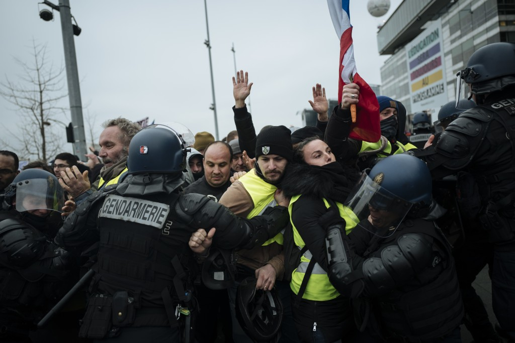 French riot police officers hold back demonstrators wearing yellow vests as they demonstrate in front of the french public television network (France
