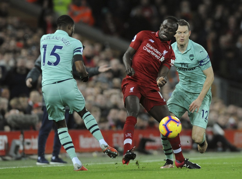 Liverpool's Sadia Mane vies for the ball with Arsenal's Ainsley Maitland-Niles during the English Premier League soccer match between Liverpool and Ar...