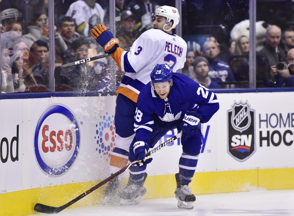 Toronto Maple Leafs right wing Connor Brown (28) collides with New York Islanders defenseman Adam Pelech (3) during the first period of an NHL hockey ...