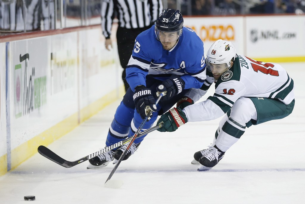Winnipeg Jets' Mark Scheifele (55) drives past Minnesota Wild's Jason Zucker (16) during second period NHL action in  Winnipeg, Manitoba, on Saturday,...