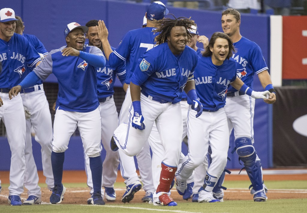 FILE - In this March 27, 2018, file photo, Toronto Blue Jays' Vladimir Guerrero Jr., center, and teammates celebrate his home run against the St. Loui...