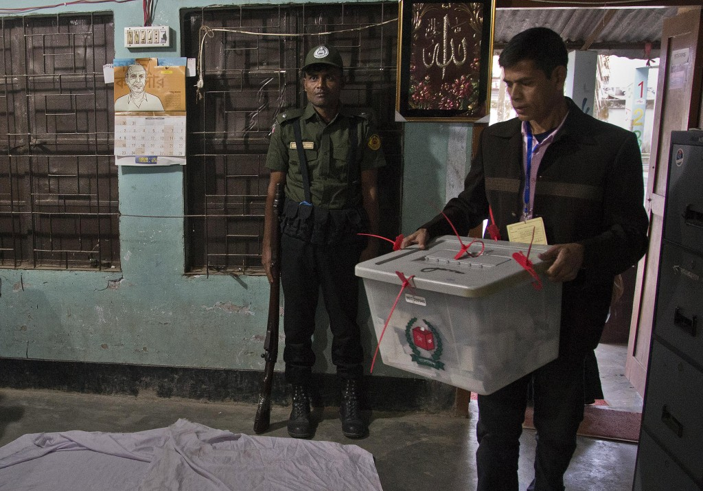 A Bangladeshi polling official carries a ballot box for counting shortly after the voting ended at a polling station in the ancient city of Panam Naga...
