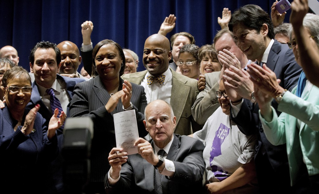 FILE - In this April 4, 2016, file photo, California Gov. Jerry Brown holds a signed bill creating the highest statewide minimum wage at $15 an hour b...