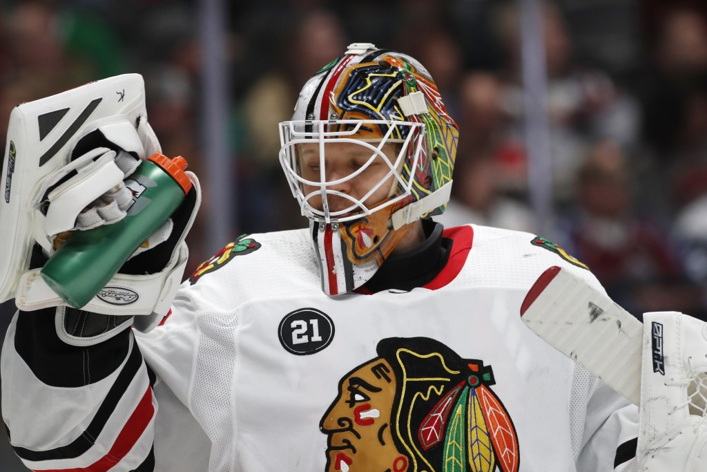 Chicago Blackhawks goaltender Collin Delia takes a drink during a timeout again the Colorado Avalanche in the first period of an NHL hockey game Satur...