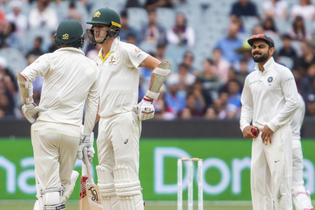 Australia's Nathan Lyon, left, and Pat Cummins, center, at the end of an over speak as India's Virat Kohli looks on during play on day five of the thi...