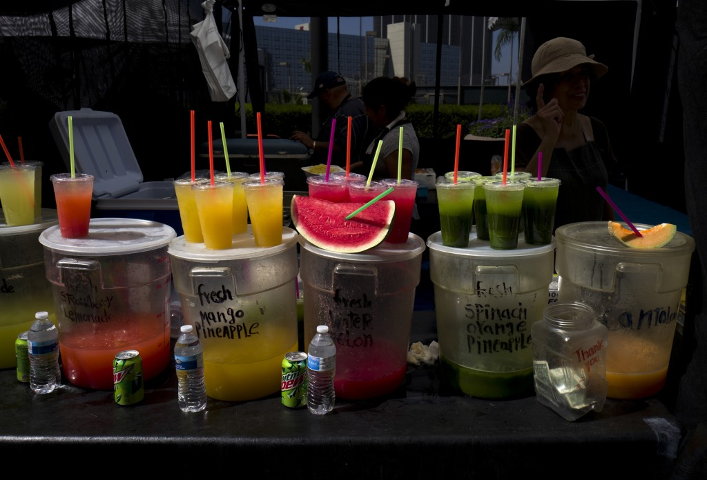 FILE - In this Sept. 21, 2018, file photo, a vendor sells fresh juices and fruit at a Farmers Market in downtown Los Angeles. A law signed Sept. 20 by...