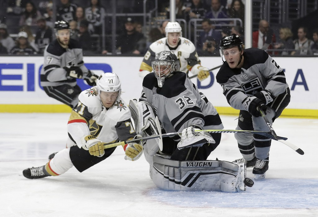 Los Angeles Kings goaltender Jonathan Quick, center, deflects a shot in front of Vegas Golden Knights' William Karlsson, left, during the first period...