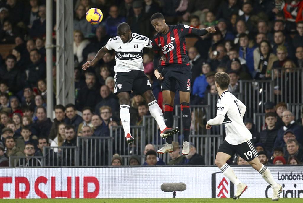 Fulham's Aboubakar Kamara, left, and Huddersfield Town's Terence Kongolo jump for a high ball during their English Premier League soccer match at Crav...