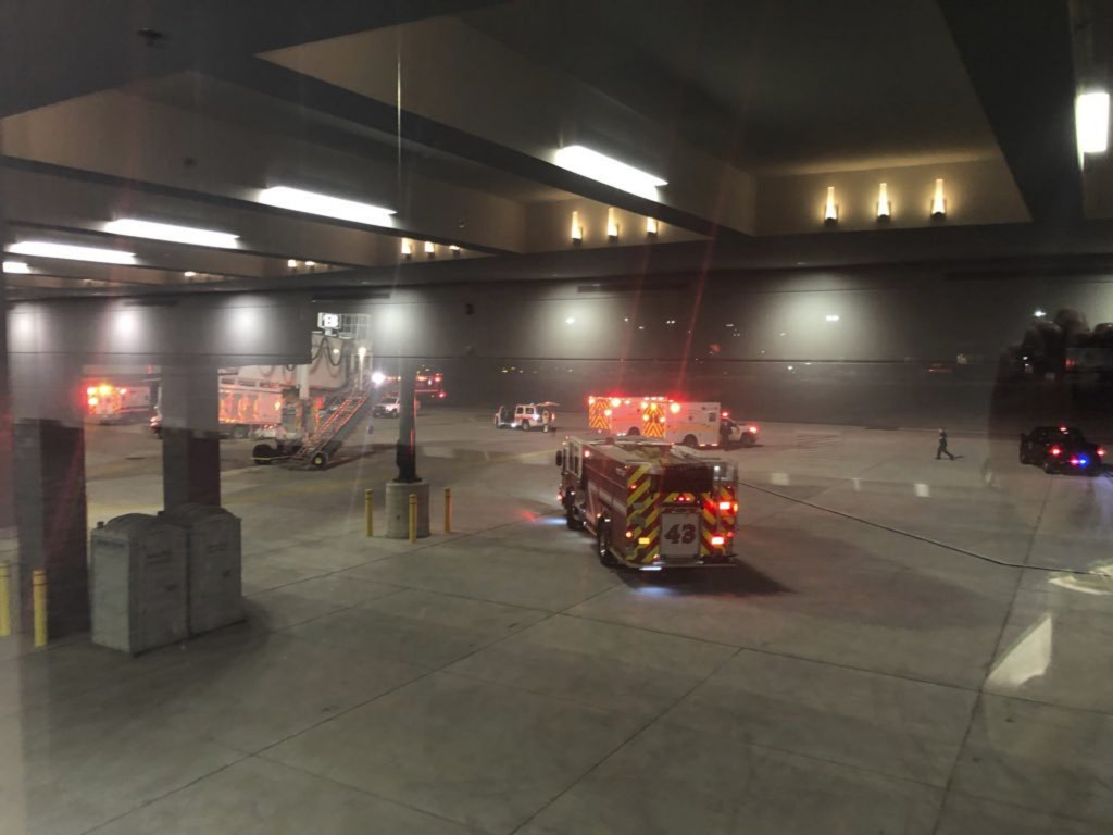 """This photo provided by Lynn Krugman and taken through a window shows emergency personnel responding after an """"equipment failure"""" involving a jet bridg..."""
